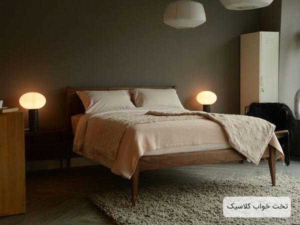 تختخواب چوبي قهوه اي رنگ مدل کلاسيک با يک عدد تشک سفيد و دو عدد آباژور رو ميزي که در کنار تخت قرار گرفته اند