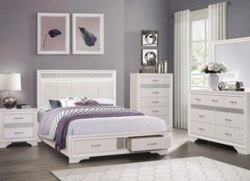 يک تخت خواب سفيد کشو دار با رو تختي هاي بنفش و تشکي به رنگ صورتي محو که يک دراور و يک ميز کنار تختي در کنار اين تخت خواب قرار گرفته اند
