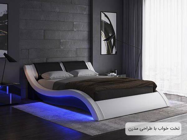 تختخوابي با طراحي مدرن و امروزي که بدنه تخت تقريبا به شکل حرف انگليسي اس با رنگ سفيد مي باشد و يک پتوي قهوه اي رنگ به همراه دو بالشت روي تخت قرار گرفته و نور آبي رنگي از قسمت زيرين تخت مي تابد