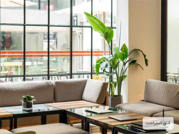 محل استراحت در يک اداره که به چندين عدد پنجره و مبلمان راحتي و گلدان و سيستم تهويه هوا مجهز مي باشد