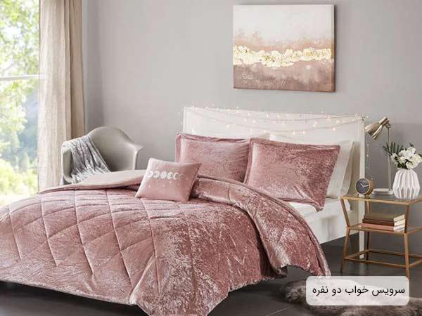 تختخواب دو نفره با پتو و بالشت هايي به رنگ صورتي روشن به همراه يک ميز کنار تختي شيشه اي و يک عدد قاب نقاشي که در بلاي تخت بر روي ديوار آويزان گشته