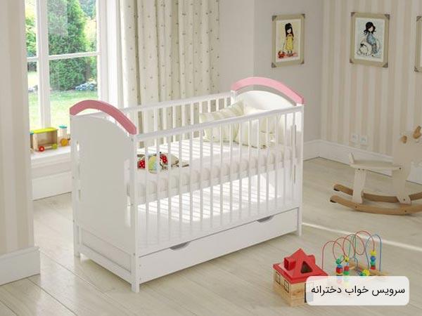 تخت خواب دخترانه مخصوص نوزاد با رنگ سفيد و صورتي که در اتاق خواب کودک قرار داده شده