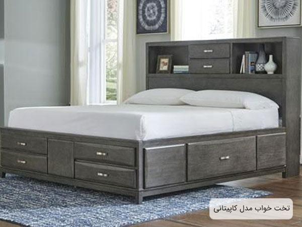 تختخواب دو نفره کشو دار يا کاپيتاني به رنگ طوسي که چند قفسه در قسمت تاج دارد