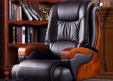 يک صندلي اداري مدرن با پشتي بلند به رنگ مشکي و بدنه قهوه اي رنگ که در يک دفتر قرار گرفته است