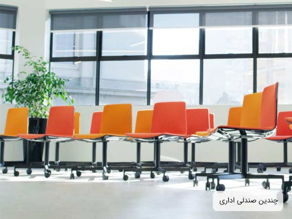 تعدادي صندلي چرخ دار مخصوص فضاهاي اداري و دفاتر کار به رنگ هاي نارنجي پررنگ و کمرنگ که در يک اداره قرار گرفته اند