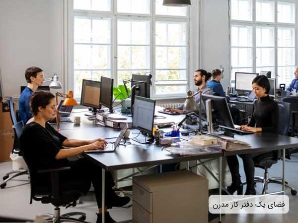 فضاهای اداری امروزي که شامل چند ميز و صندلي مي باشد و روي هر ميز يک عدد کامپيوتر قرار گرفته و کارمندان مشغول کار هستند