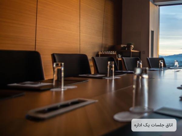 سالن جلسات يک شرکت که به يک ميز جلسه و چندين صندلي مجهز مي باشد و روي ميز تعداد ليوان و کاغذ و دستمال کاغذي قرار گرفته