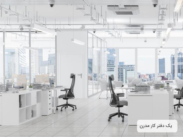 نمايي از يک دفتر کار مدرن با ديوار ها و ميز هاي سفيد رنگ که در کنار هر ميز يک عدد صندلي مشکي وجود دارد و بر روي هر ميز يک عدد کامپيوتر قرار گرفته است