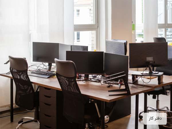 محيط يک اداره که شامل چندين ميز و صندلي است و روي هر ميز يک کامپيوتر قرار گرفته