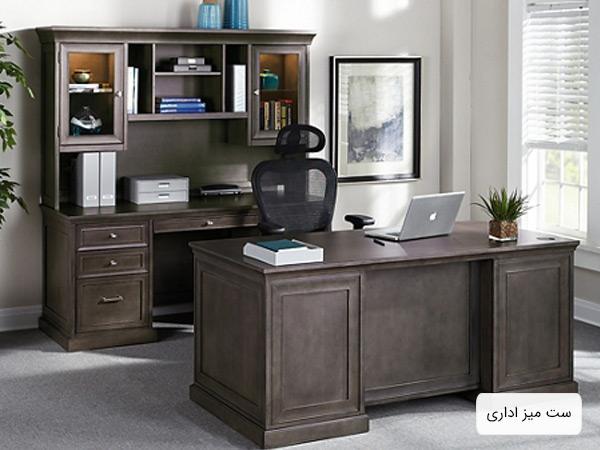 يک عدد ميز اجرايي به همراه يک ميز قفسه دار به رنگ قهوه اي در کنار يک صندلي که يک عدد لپ تاپ روي ميز اجرايي قرار گرفته است