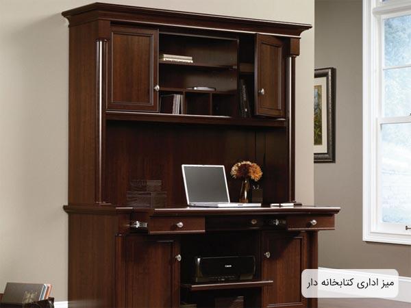 ميز قفسه دار يا کتابخانه دار مناسب محيط هاي اداري يه رنگ قهوه اي که يک عدد لپ تاپ بر روي آن قرار گرفته است
