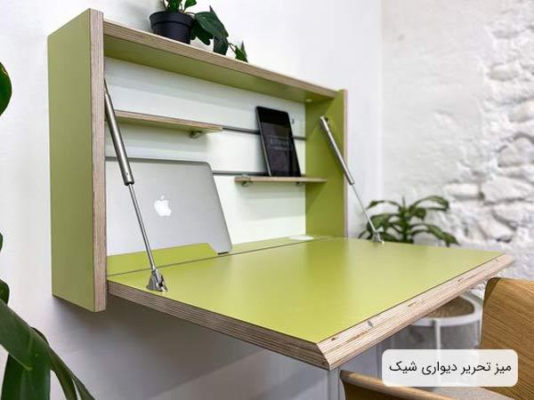 ميز تحرير ديواري ام دي اف سبز رنگ و داراي دو قفسه که يک عدد لپ تاپ بر روي آن قرار گرفته است