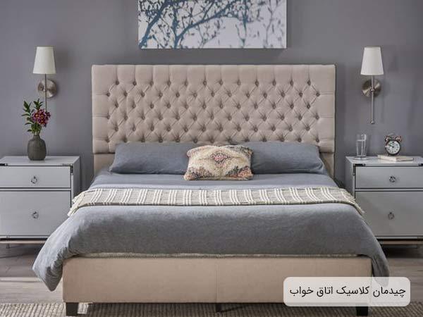 نمايي از يک اتاق خواب مجهز به يک تختخواب دو نفره و دو عدد ميز کنار مبلي دو طبقه سفيد رنگ به همراه دو عدد آباژور ديواري و يک تابلوي نقاشي