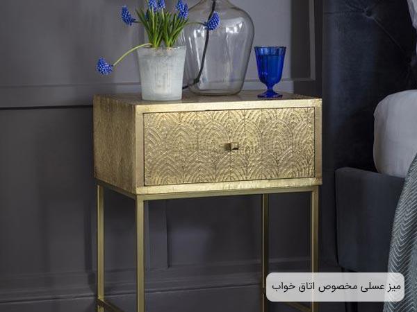 ميز طلايي رنگ براي کنار تخت که داراي کشو بوده و لوازم دکوري از جمله يک گلدان با گل هاي آبي رنگ و يک ليوان به همان رنگ آبي بر روي تخت قرار گرفته اند
