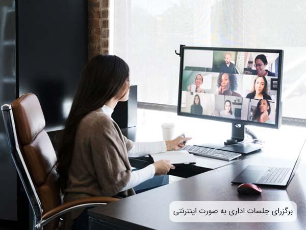 يک عدد ميز و صندلي کار که کارمندي روي صندلي نشسته و با استفاده از يک لپ تاپ در يک جلسه مجازي شرکت نموده