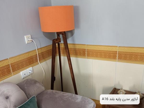 تصويری از آباژور A16 با شيد نارنجی رنگ که در کنار يک مبل خاکستری رنگ قرار گرفته است.