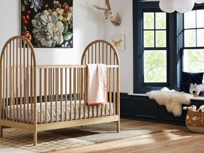 تصويری از يک تخت نوزاد کرمی رنگ چوبی که در اتاق خواب کودک قرار گرفته است .