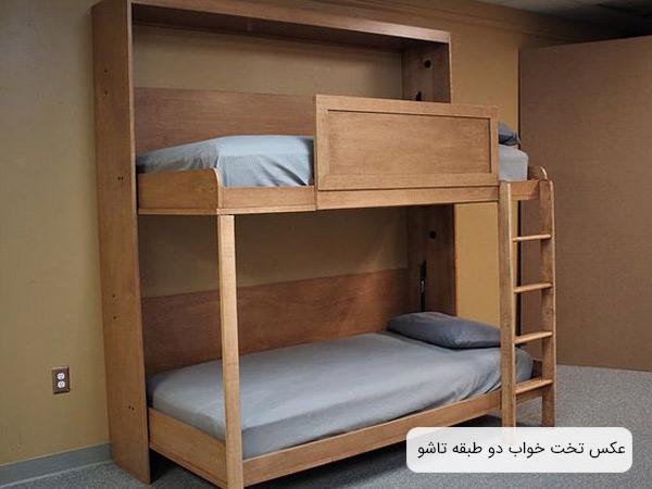 تخت دو طبقه ديواری با بدنه قهوه ای رنگ و تشک نقره ای رنگ در اتاقی با ديوار های قهوه ای.