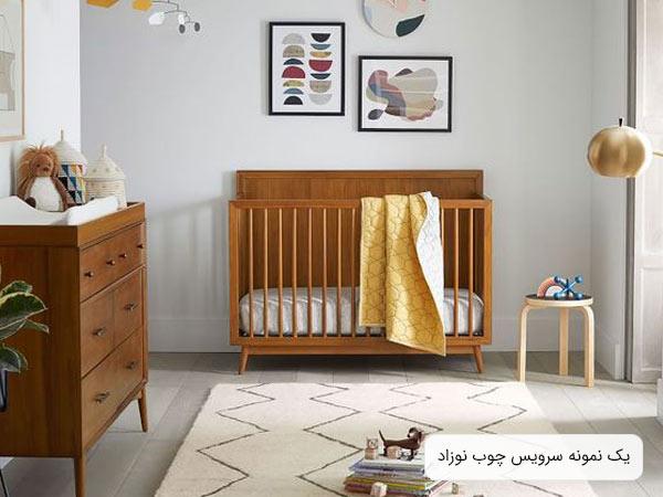 تصويری از سرويس خواب چوبی نوزاد به رنگ قهوه ای که شامل يک تخت نوزاد و يک دراور می باشد و اتاق خواب نوزاد با لوازم دکوری تزئين گشته است.
