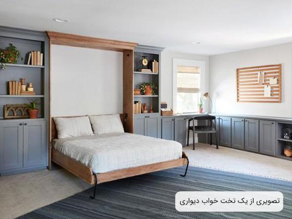 تصويری از يک تختخواب ديواری تاشو به رنگ قهوه ای روشن و قفسه هايی به رنگ خاکستری و تعدادی از لوازم دکوری که در قفسه ها قرار گرفته اند.