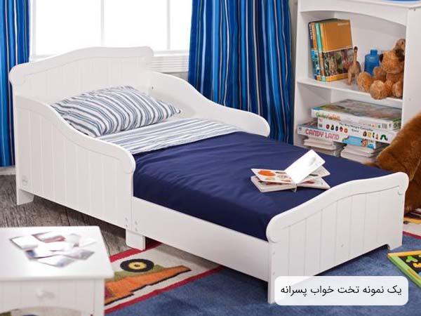 تصويری از يک تخت پسرانه با بدنه ای به رنگ سفيد و خوشخوابی به رنگ های آبی تيره و سفيد که يک عدد کتاب داستان کودکانه روی تخت قرار گرفته است.