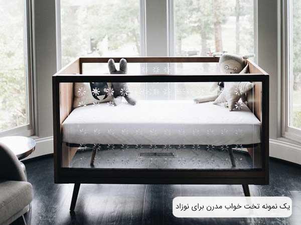 تصوير يک سروس خواب مدرن نوزاد که بجای نرده از شيشه در بدنه اين تخت استفاده شده و ديواره های اين تخت به رنگ قهوه ای می باشد و دو عدد عروسک داخل تخت گذاشته شده است.
