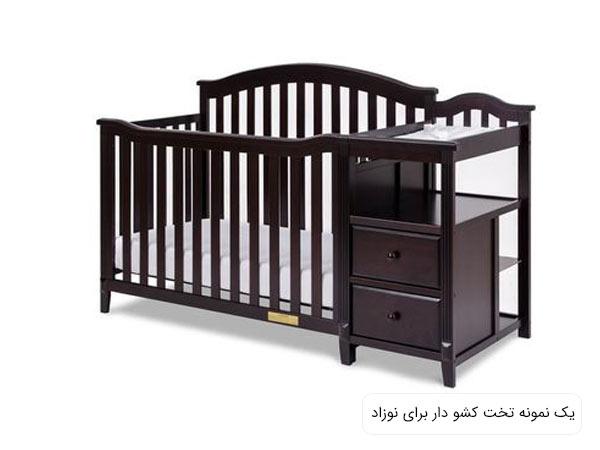 تصويری از يک تخت خواب نوزاد زرشکی رنگ و دارای کشو در پس زمينه سفيد.