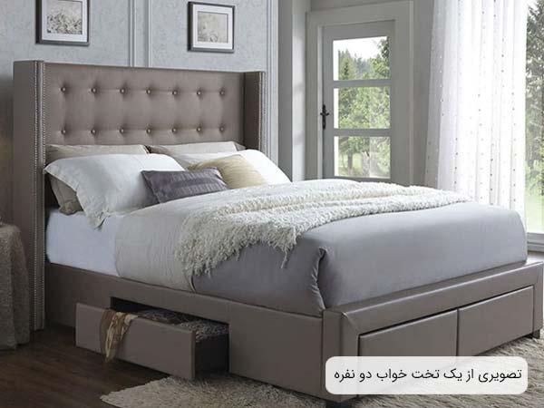 عکس يک تخت خواب دو نفره کشو دار که رنگ بدنه آن طوسی روشن بوده و خوش خواب با رنگ های مختلف روی آن قرار گرفته است.
