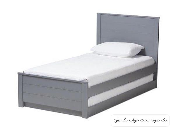 تصويری از يک تخت خواب يک نفره ساده و شيک با بدنه ای به رنگ طوسی و تشک سفيد در پس زمينه سفيد.