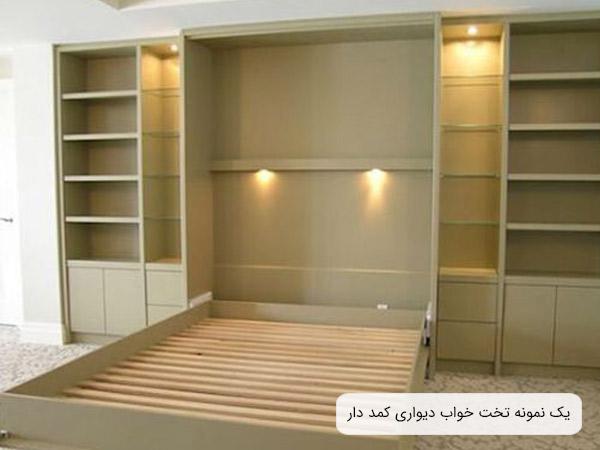 تصوير از يک تخت ديواری خواب دو نفره به رنگ گندمی تيره که خوشخواب و ... روی آن قرار نگرفته و قفسه ها خالی می باشد.