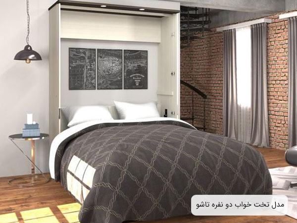 يک نمونه تخت خواب تاشو و ديواری به رنگ سفيد و پتويی به رنگ طوسی که يک عدد ميز کنار تختی گرد در کنارش قرار گرفته است.