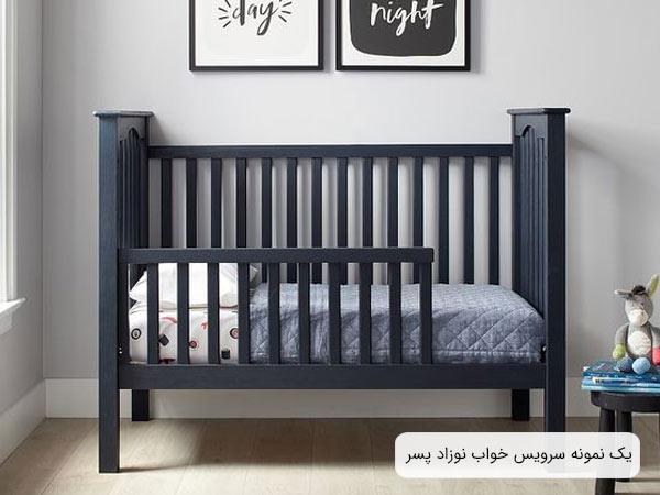تصويری از يک تخت خواب نوزاد به رنگ سرمه ای و خوشخوابی با رنگ های ذغالی روشن و سفيد و دو عدد تابلوی دکوری که بر روی ديوار نصب گشته اند.