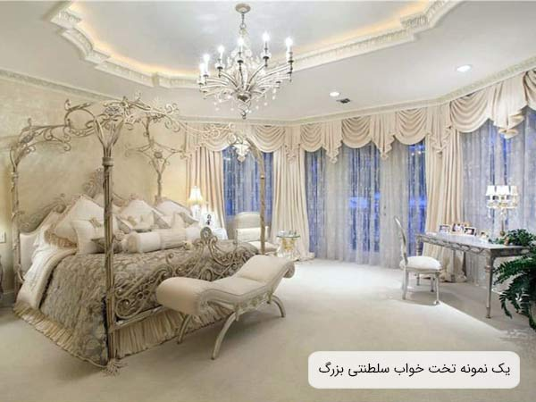 تصويری از يک تخت خواب سلطنتی با سايز بزرگ و به رنگ سفيد و ستون دار که ظاهر بسيار لوکس و شيکی داشته و در يک اتاق با طراحی کلاسيک و زيبا قرار گرفته است.