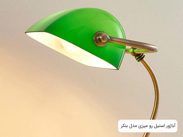 تصوير آباژور مدل بنکر با قاب شيشه اي سبز رنگ که لامپ ان روشن شده است.