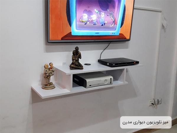 تصويري از زير تلويزيوني ساده و شيک به رنگ سفيد که بر روي ديوار نصب گشته است