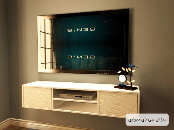 تصويری از ميز تلويزيون FH261 مدل ديواری به رنگ سفيد که بر روی ديوار نصب گشته است و يک عدد تلويزيون ال سی دی بر روی آن قرار گرفته است