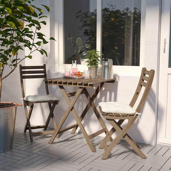 ميز و صندلی تاشو مخصوص ناهار خوری به رنگ قهوه ای که در کنار يک گلدان قرار گرفته اند و چند وسيله بر روی آنها قرار گرفته است