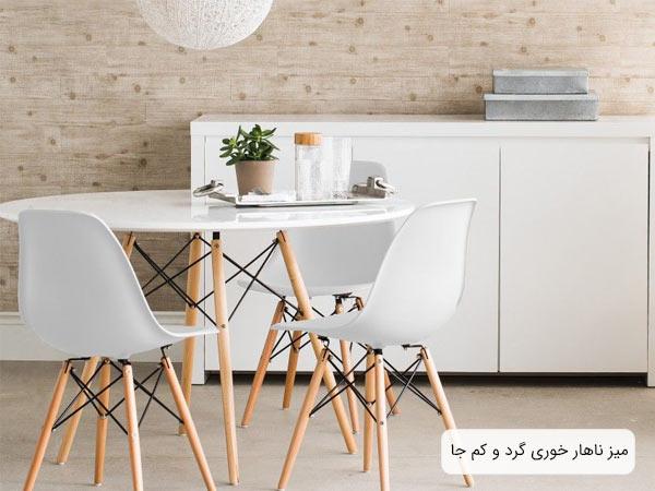 ست ميز صندلی ناهار خوری سفيد رنگ با پايه های کرمی رنگ که چند عدد وسيله از جمله يک گلدان کوچک روی اين ميز قرار گرفته است.