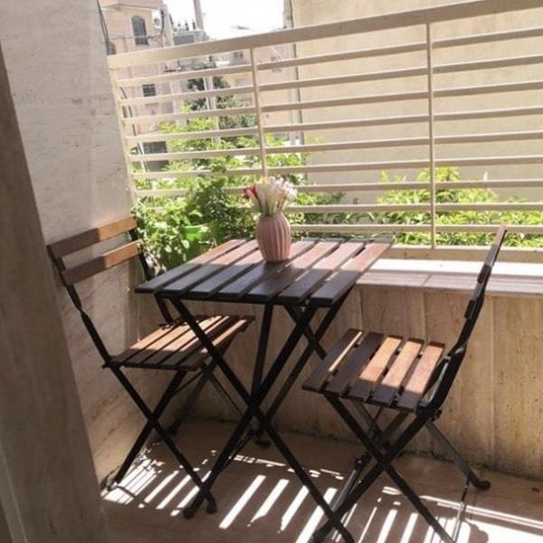 ميز ناهار خوری تاشو و کم جا به رنگ قهوه ای در کنار صندلی ناهار خوری مدرن