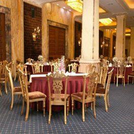 ميز ناهار خوری سلطنتی سپهر به رنگ طلايی و رو ميزی هايی قرمز رنگ به همراه چند صندلی ناهار خوری سلطنتی که دور اين ميز قرار داده شده اند.