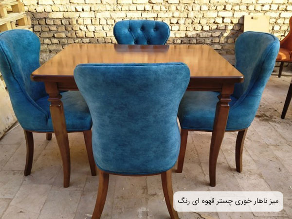 ميز ناهارخوری چستر چهار نفره در کنار چهار عدد صندلی ناهار خوری آبی رنگ.
