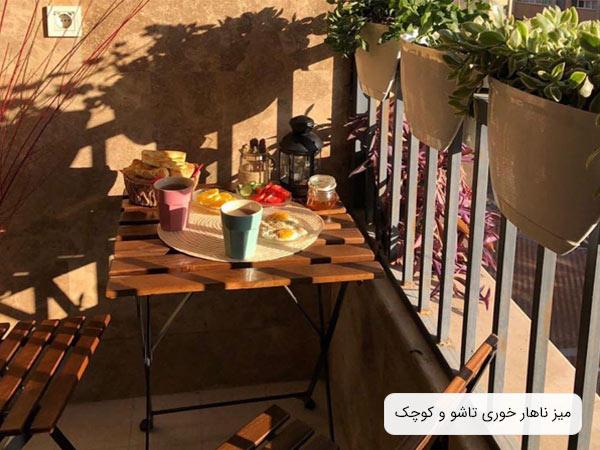 ميز و صندلی ناهار خوری مدرن به رنگ قهوه ای و جنس چوبی در يک بالکن در کنار چندين گلدان و غذاهايی که روی ميز قرار گرفته است