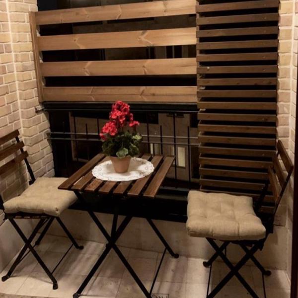 ميز ناهار خوری دو نفره کوچک با سطح چوبی و قابليت تاشو به رنگ قهوه ای به همراه دو صندلی غذا خوری چوبی