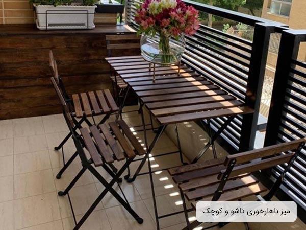 ميز ناهار خوری کم جا تارنو چوبی دو نفره مربع شکل و تا شونده به رنگ قهوه ای در کنار دو عدد صندلی ناهار خوری مدرن