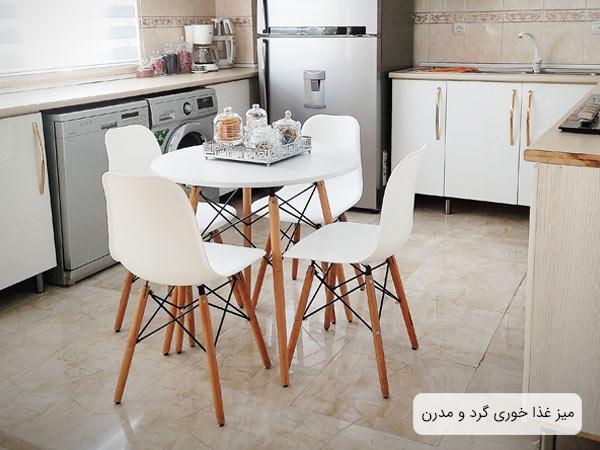 ميز ناهار خوری مدرن و گرد ای 411 به رنگ سفيد به همراه چند عدد صندلی ناهار خوری سفيد که در کنار اين ميز قرار گرفنه اند