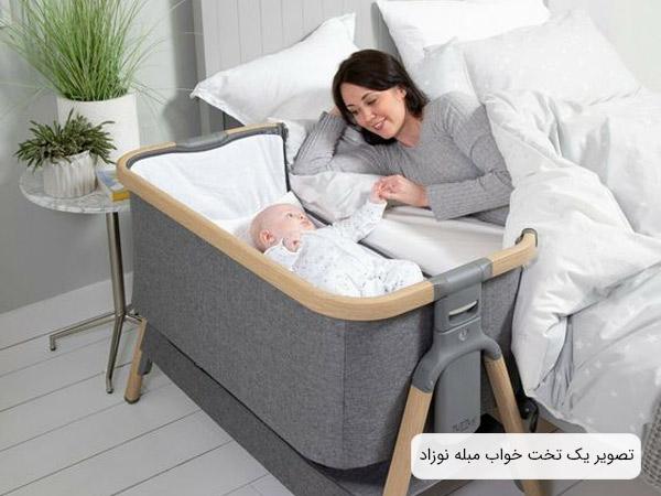 عکس يک تخت مبله برای نوزاد که در کنار يک تخت خواب قرار داده شده و يک کودک درون تخت نوزاد قرار گرفته است.