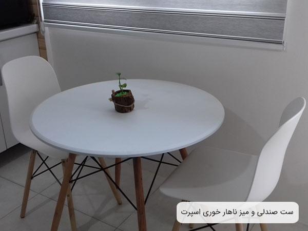 دو عدد صندلی ناهار خوری آريا MP44 در کنار يک ميز ناهار خوری اسپرت سفيد رنگ با پايه های کرمی رنگ .