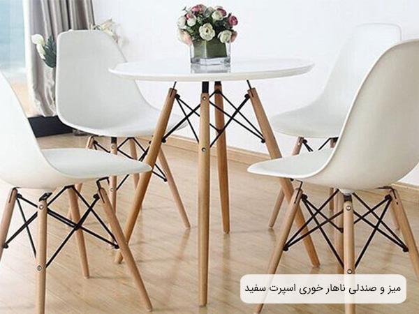 تصويری از ست ميز و صندلی کروماتيک سفيد رنگ با پايه های کرمی رنگ و يک عدد گلدان که روی ميز قرار گرفته است.