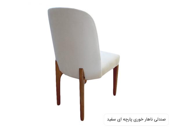 صندلی غذا خوری پارچه ای به رنگ سفيد و پايه های قهوه ای در پس زمينه سفيد.