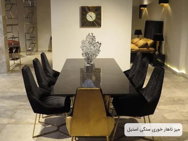 تصويری از ميز ناهار خوری استيل مدل آريسا با سطح سنگی به همراه 7 عدد صندلی ناهار خوری استيل مشکی رنگ و يک عدد گلدان نقره ای رنگ که روی ميز قرار گرفته است.